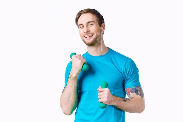 Mann mit hanteln in den händen blaues t-shirt trainieren fitness-kopfhörer