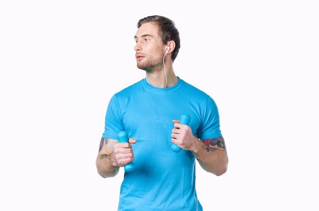 Mann mit hanteln in einem blauen t-shirt auf einem hellen hintergrund, der zur seitlichen beschnittenen ansicht schaut