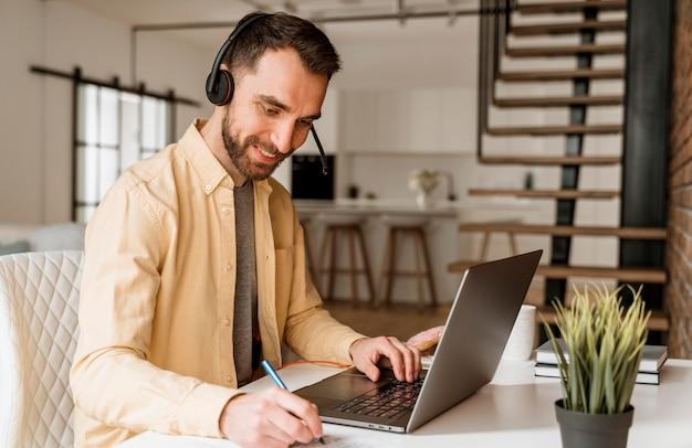 Mann mit headset, der videoanruf auf laptop hat