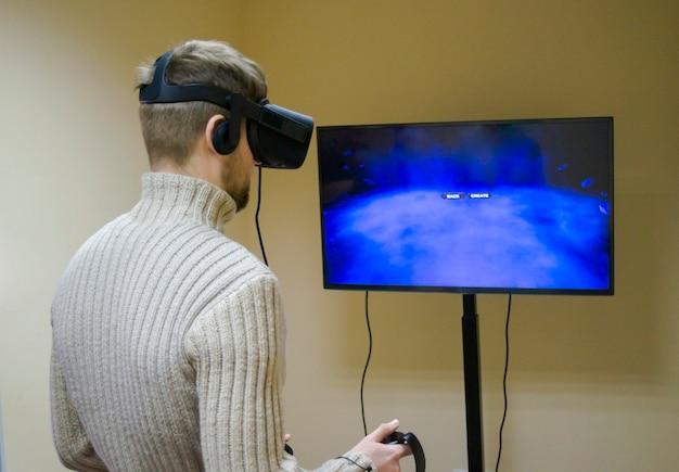 Mann mit helm virtual reality spielt ein spiel
