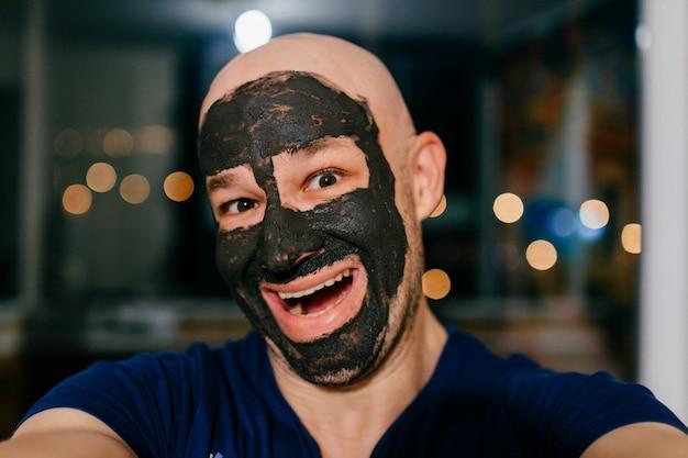 Mann mit holzkohlenmaske auf seinem gesicht, das selfie nimmt