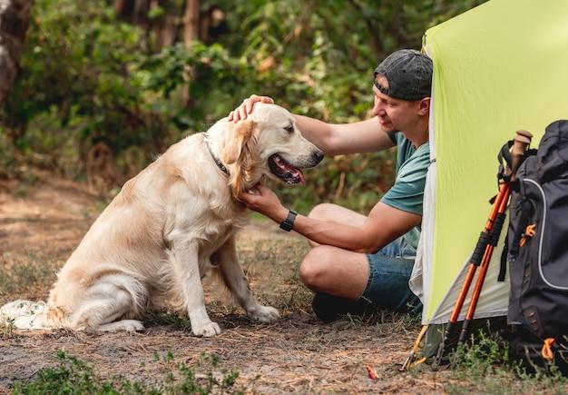 Mann mit hund, der neben zelt in der natur sitzt