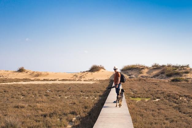 Mann mit hund geht auf dem holzweg am strand spazieren und schaut in die ferne des ozeans. Premium Fotos
