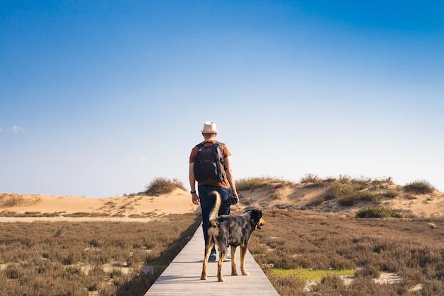 Mann mit hund geht auf dem holzweg am strand spazieren und schaut in die ferne des ozeans.