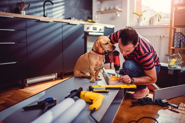 Mann mit hund küchenschränke bauen und mit einem akku-bohrer