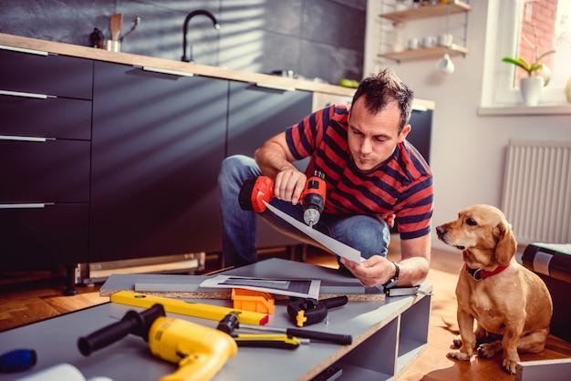 Mann mit hund pläne beim errichten von küchenschränken überprüfend