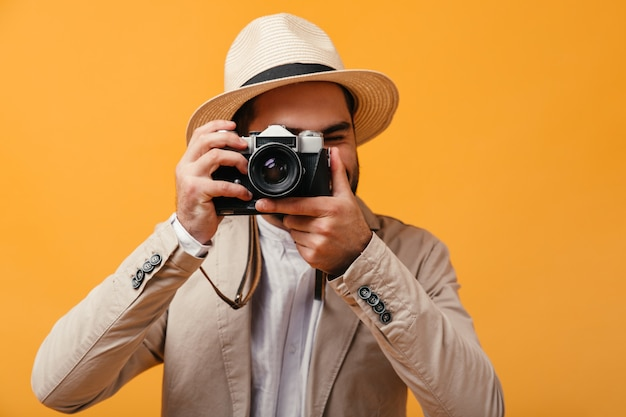 Mann mit hut mit breiter krempe fotografiert mit retro-kamera