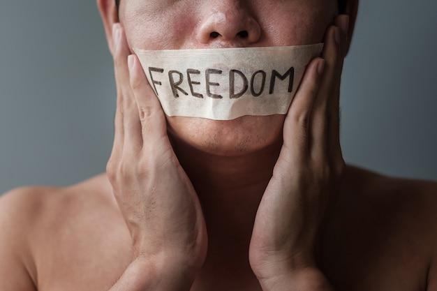 Mann mit in klebeband versiegeltem mund mit freiheitsbotschaft. meinungsfreiheit, pressefreiheit, menschenrechte, protestdiktatur, demokratie, freiheit, gleichheit und brüderlichkeitskonzepte