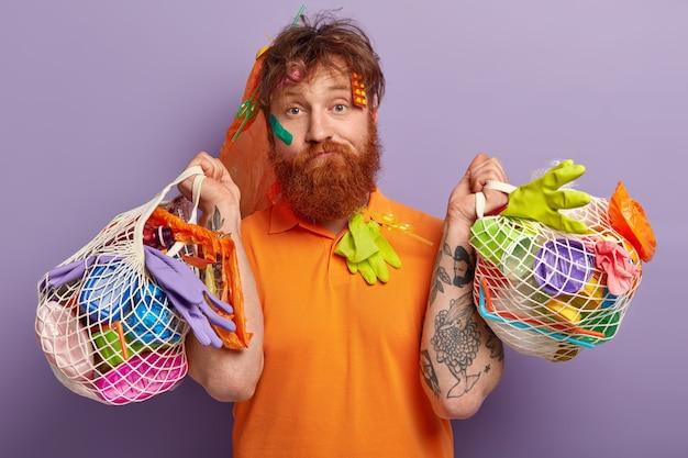 Mann mit ingwerbart, der taschen mit plastikmüll hält