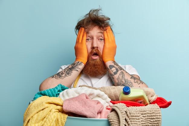 Mann mit ingwerbart, der wäsche tut