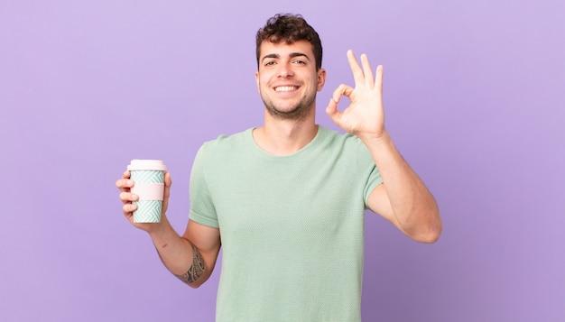 Mann mit kaffee, der sich glücklich, entspannt und zufrieden fühlt, zustimmung mit okayer geste zeigt und lächelt