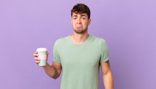 Mann mit kaffee, der traurig und weinerlich mit einem unglücklichen blick ist und mit einer negativen und frustrierten einstellung weint