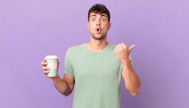 Mann mit kaffee sieht ungläubig aus, zeigt auf ein objekt an der seite und sagt wow, unglaublich