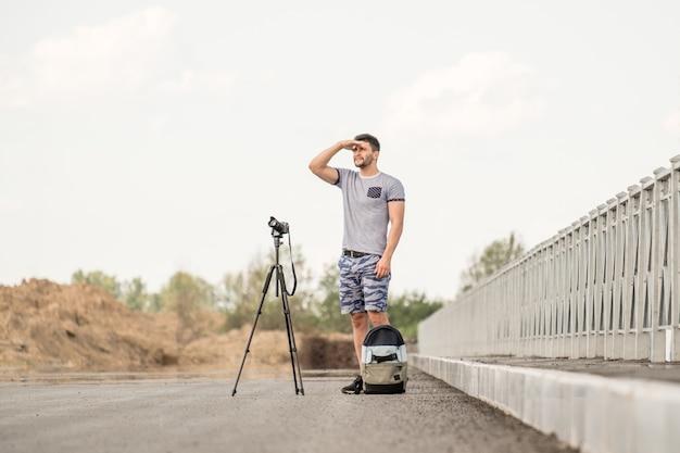 Mann mit kamera auf stativ