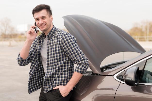 Mann mit kaputtem auto, das über telefon spricht