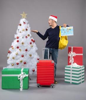 Mann mit kartenpunktfinger, der weihnachtsbaum auf grau lokalisiert zeigt