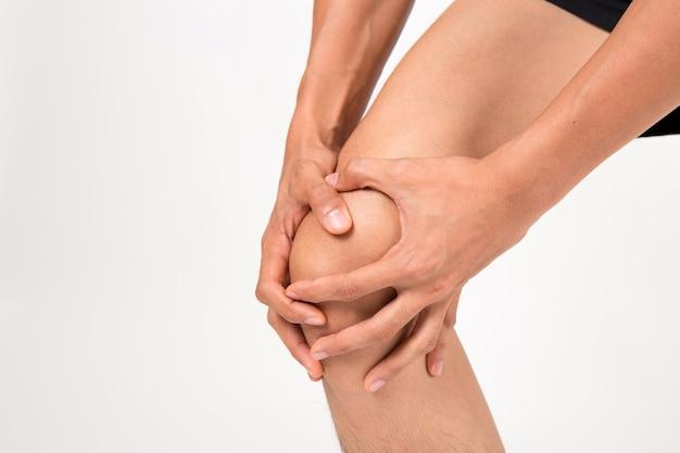 Mann mit kniegefühlsschmerz. atelieraufnahme auf weißem hintergrund. fitness- und gesundheitskonzept