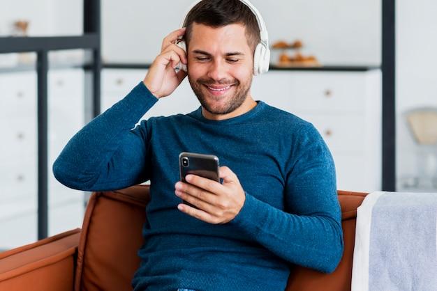 Mann mit kopfhörer an und mobile in der hand