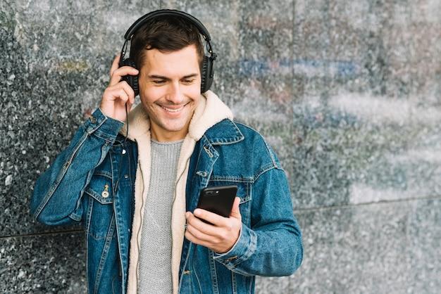 Mann mit kopfhörer und smartphone in der städtischen umwelt
