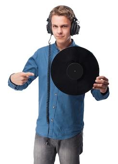 Mann mit kopfhörern auf einem vinyl zeigen