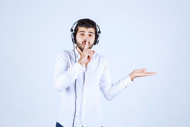 Mann mit kopfhörern bittet um stille.