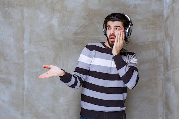 Mann mit kopfhörern, der mit jemandem beiseite interagiert