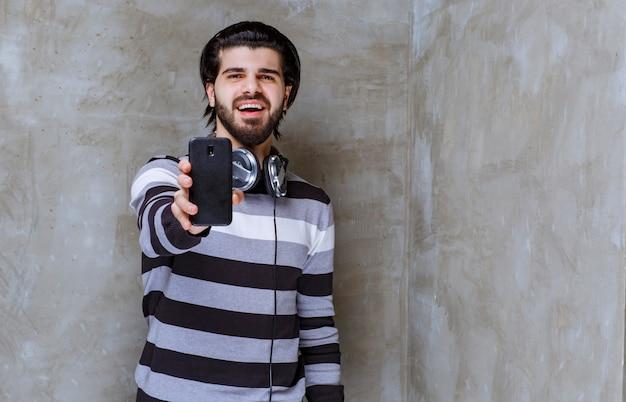 Mann mit kopfhörern, der sein schwarzes smartphone demonstriert