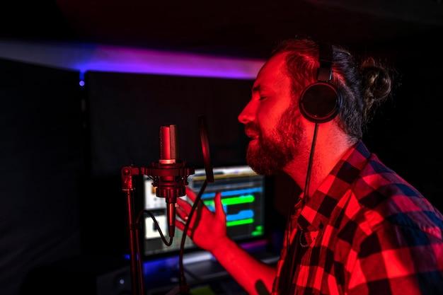 Mann mit kopfhörern singt im mikrofon im radio und sendet sein brandneues lied
