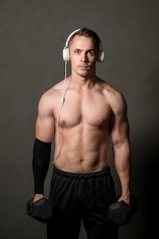 Mann mit kopfhörern und gewichten