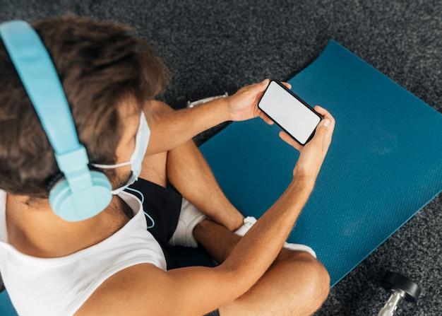 Mann mit kopfhörern und medizinischer maske, die smartphone am fitnessstudio betrachten