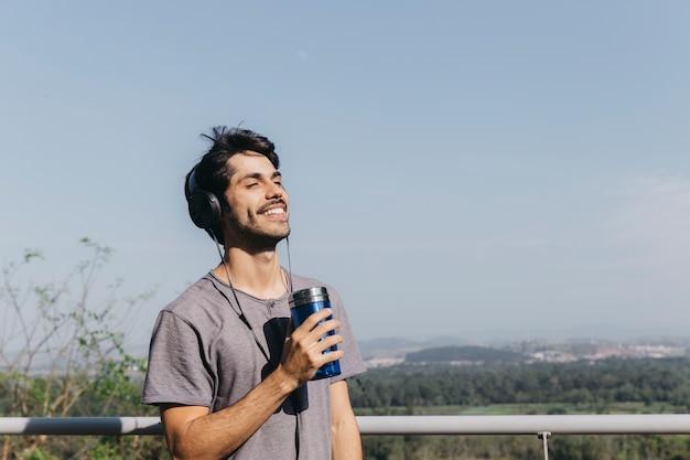 Mann mit kopfhörern und thermocup