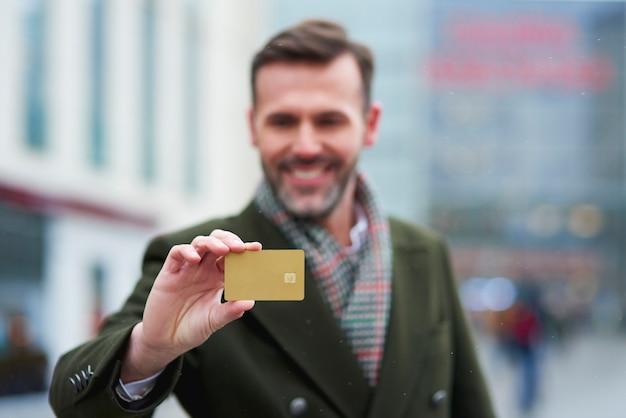 Mann mit kreditkarte beim großen einkauf