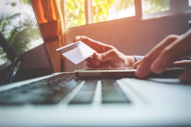 Mann mit kreditkarte in der hand und eingabe sicherheitscode mit smartphone auf laptop-tastatur, online-shopping-konzept.