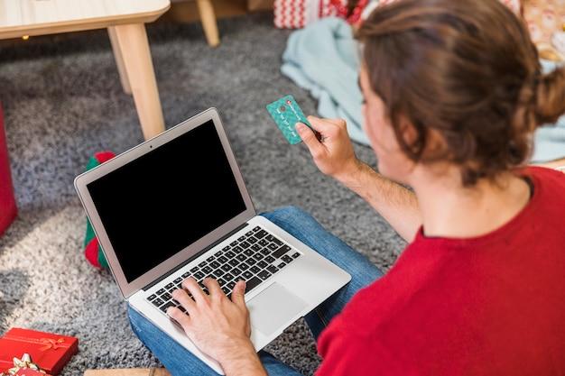 Mann mit kreditkarte unter verwendung des laptops