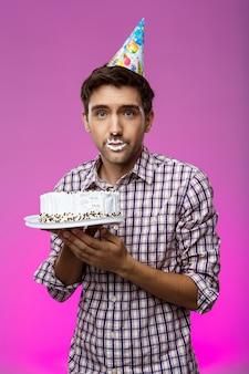 Mann mit kuchen auf den lippen über lila wand. geburtstagsfeier.