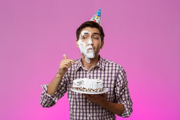 Mann mit kuchen auf gesicht über lila wand. geburtstagsfeier.