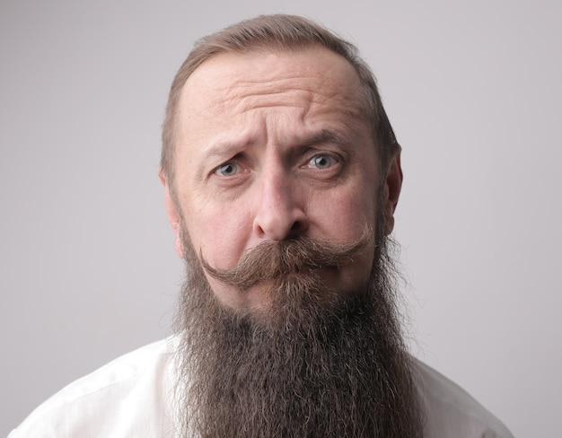 Mann mit langem bart und stirnrunzelndem schnurrbart vor einer grauen wand