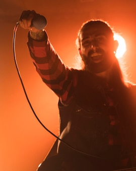 Mann mit langen haaren, der das mikrofon hält