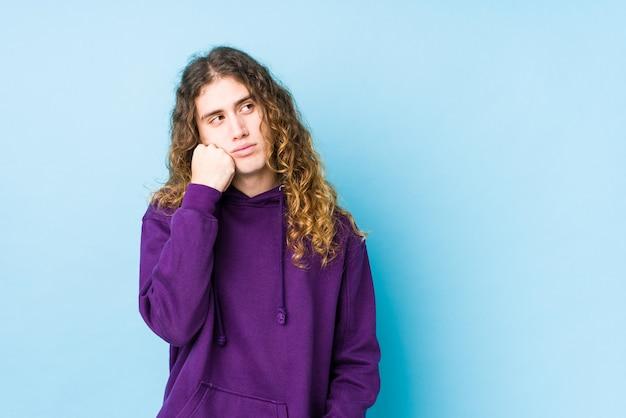 Mann mit langen haaren posiert isoliert, der sich traurig und nachdenklich fühlt und den kopierraum betrachtet.