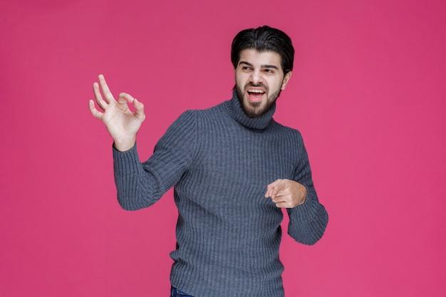 Mann mit langen haaren und bart, der nullkreiszeichen in der hand macht.