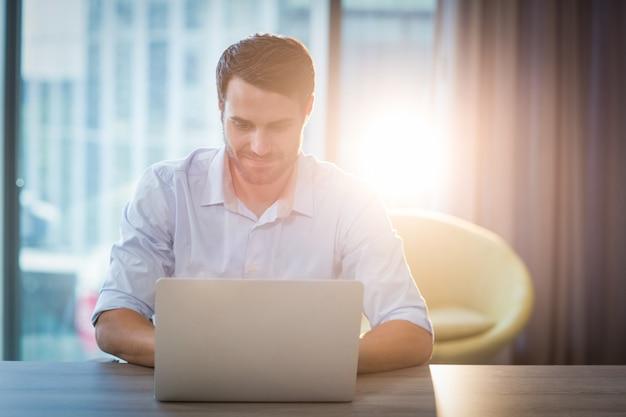 Mann mit laptop an seinem schreibtisch