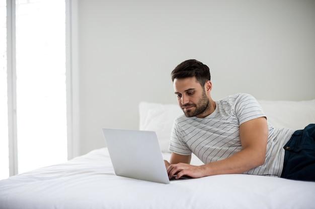 Mann mit laptop auf bett im schlafzimmer
