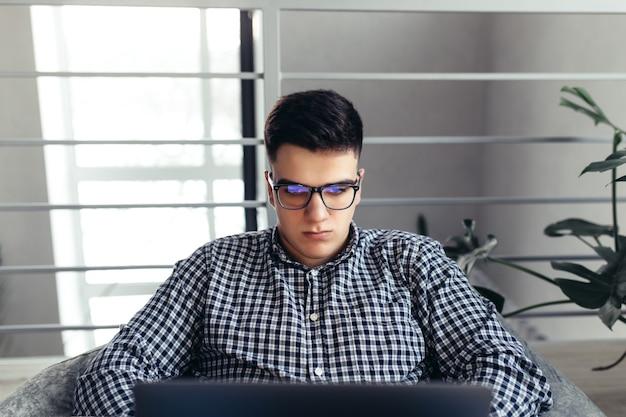 Mann mit laptop, brille, gepolsterte möbel. unscharfer hintergrund