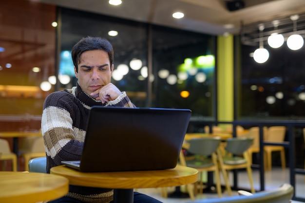 Mann mit laptop-computer beim denken