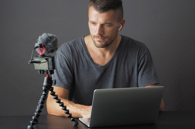 Mann mit laptop, der vlog auf digitalkamera mit mikrofon aufzeichnet