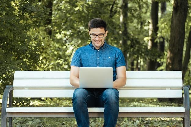 Mann mit laptop im stadtpark