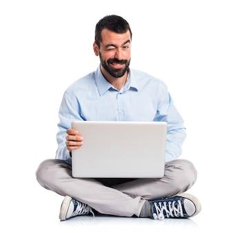 Mann mit laptop mit bauchschmerzen