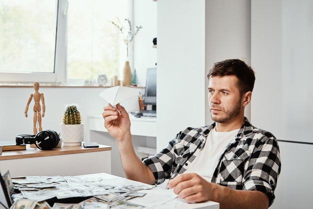 Mann mit laptop und dollar-banknoten spielt mit papier