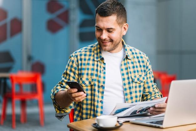 Mann mit laptop unter verwendung des smartphone im café
