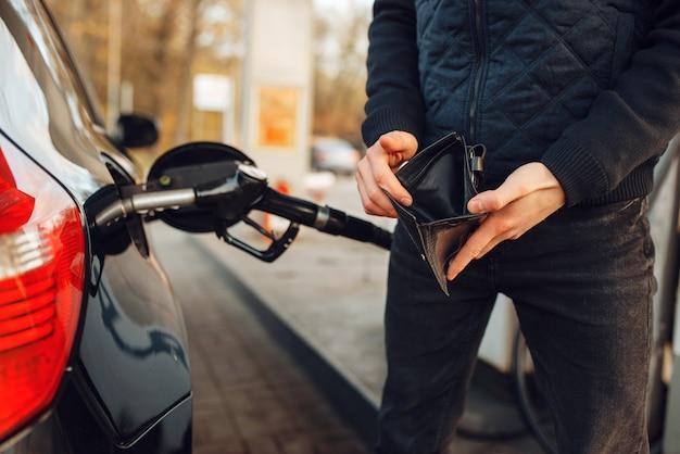 Mann mit leerem geldbeutel an tankstelle, tankfüllung. benzintanken, benzin- oder dieseltankservice